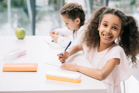 african american schoolgirl smiling at camera while classmate studying behind in class