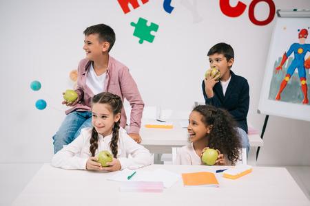 휴식 시간에 교실에 앉아있는 동안 사과를 먹는 아이들 스톡 콘텐츠