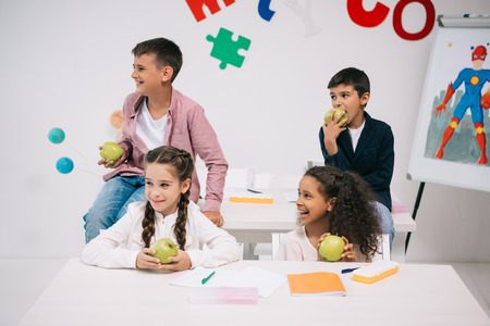 children eating apples while sitting in classroom during break