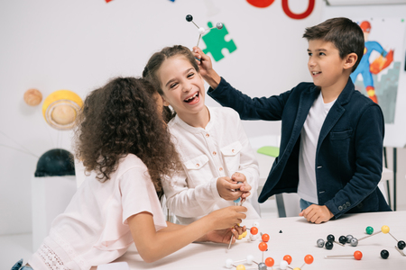 multiethnic schoolchildren working with molecular model and smiling in class