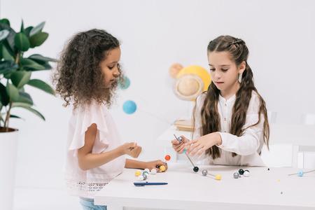 multiethnic schoolgirls working with molecular model at chemistry class Stock Photo