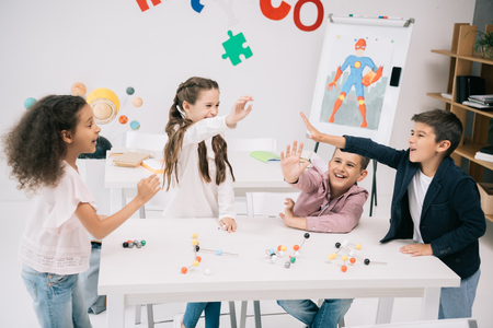 schoolkids giving high five while studying with molecular model in classroom