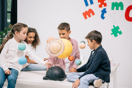 schoolchildren working with solar system model in classroom Imagens
