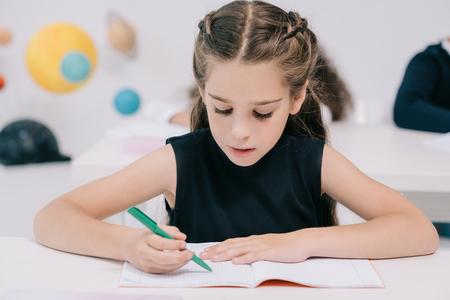 귀여운 집중된 여학생은 수업에서 운동 서를 작성