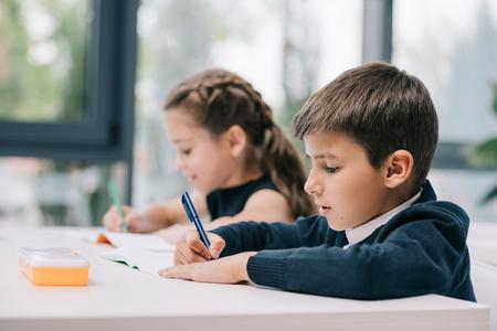 spolužáků sedí u stolu a psaní v cvičení