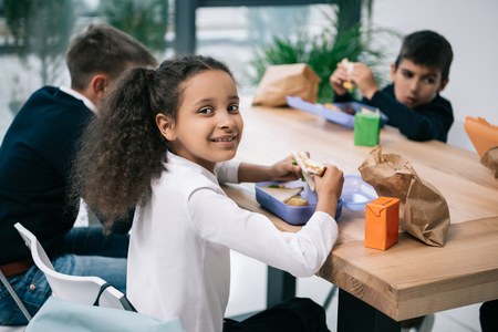 multiethnic schoolkids eating lunch while sitting at table