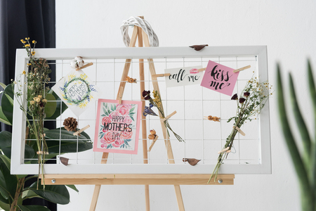 creative board with greeting cards and dry flowers standing in office