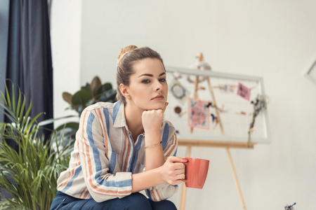 thoughtful businesswoman with coffee cup sitting in modern office Banco de Imagens