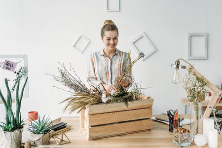 attractive female florist with dry flowers at workplace Banco de Imagens