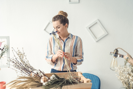 female florist working with dry flowers at workplace