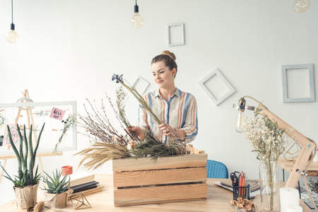 attractive female florist working with dry flowers at workplace Banco de Imagens