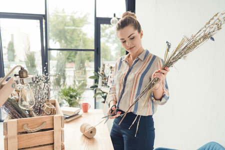 female decorator working with dry flowers at workplace