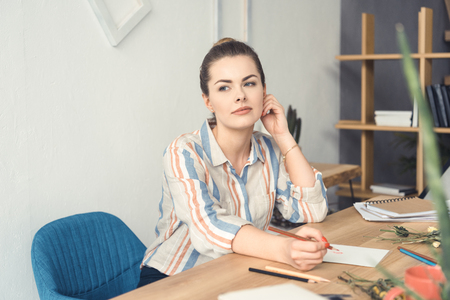 attractive businesswoman writing something at workplace