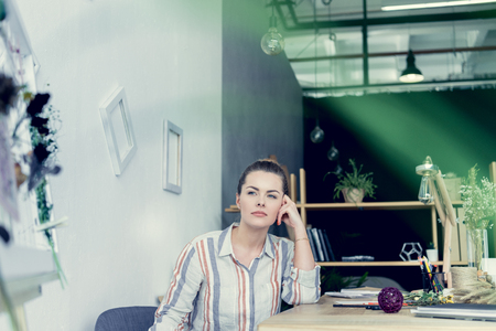 attractive businesswoman sitting at table in modern office