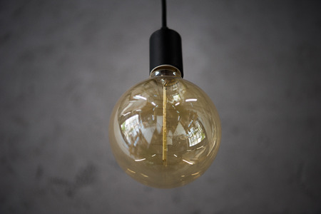 big vintage light bulb hanging from grey ceiling