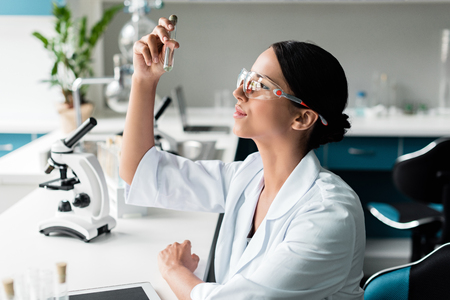 young chemist in protective glasses and white coat examining test tube in lab Stock Photo