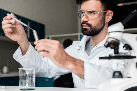 male scientist in protective glasses making experiment in chemical lab