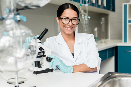 young scientist in eyeglasses working with microscope and smiling at camera in chemical lab