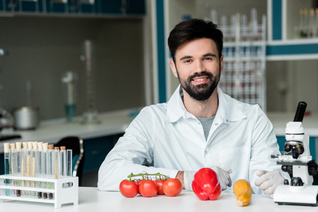 young scientist examining vegetables and smiling at camera in laboratory Stock Photo