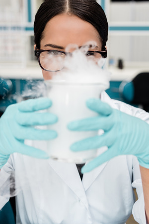 female scientist in eyeglasses holding flask while making experiment in chemical lab