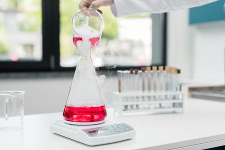 화학 실험실에서 전자 저울에 플라스크에 시약을 붓는 과학자