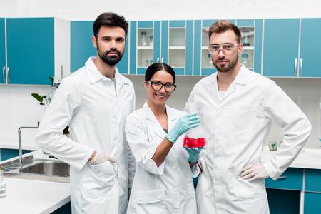 jonge wetenschappers in witte jassen houden kolf met reagens en glimlachen naar de camera in chemisch laboratorium
