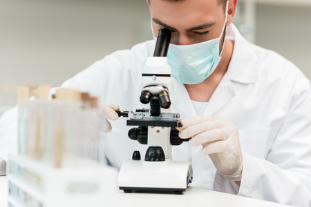 concentrated young scientist in protective mask working with microscope in chemical lab