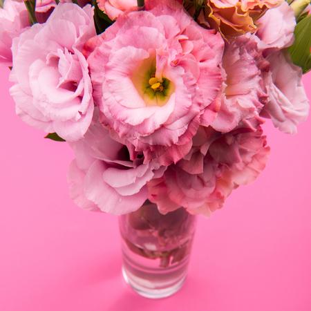 Close-upmening van mooi teder roze eustoma bloemenboeket in vaas