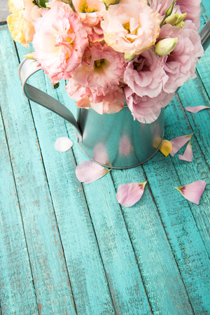 beautiful tender flowers in watering can and pink petals on wooden surface 版權商用圖片 - 84187419