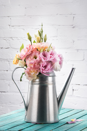 table top: beautiful tender eustoma flowers with buds in watering can on wooden table