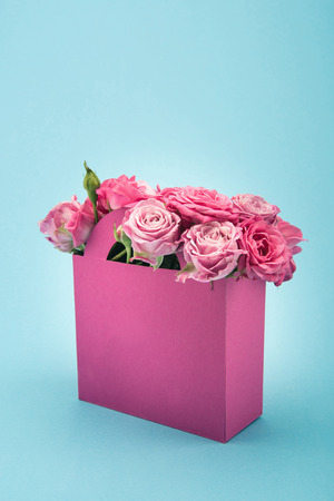 beautiful blooming pink roses in decorative paper bag arranged isolated on blue Imagens