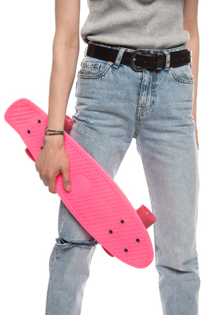 Cropped shot of young woman holding pink skateboard