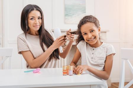 アフリカ系アメリカ人の娘が彼女の髪をとかす母親ながらマニキュアをしています。 写真素材
