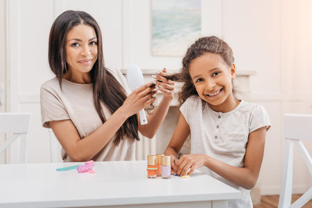 african american daughter doing manicure while mother combing her hair