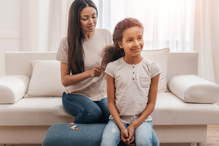 afro american mother combing hair to little daughter at home Stock Photo