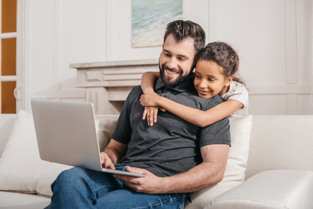 domestic: father with daughter sitting on sofa and using laptop at home
