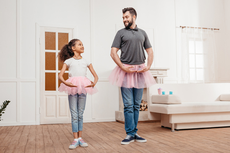 domestic: family in pink tutu tulle skirts dancing at home Stock Photo