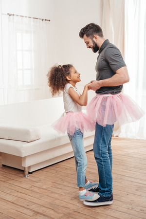 father and daughter in pink tutu tulle skirts dancing together