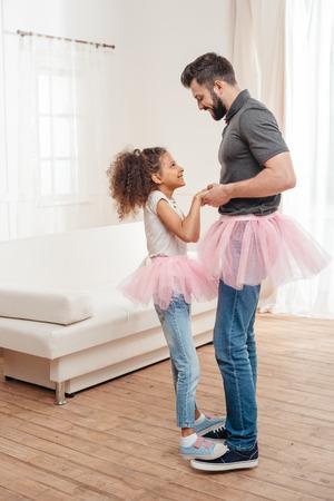 Vater und Tochter in rosa Tutu Tüll Röcke tanzen zusammen Standard-Bild - 84187372