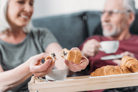 senior couple having breakfast with croissants in bed