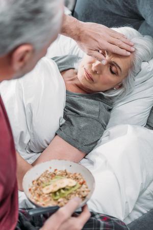 Mann kümmert sich um kranke Frau im Bett Standard-Bild - 84372754