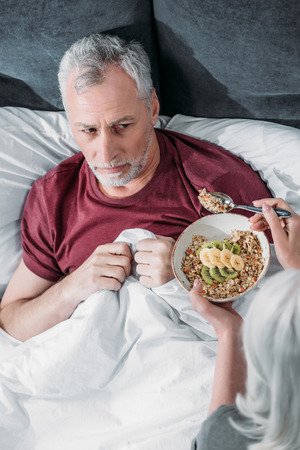 woman taking care of sick husband in bed at home Stock Photo