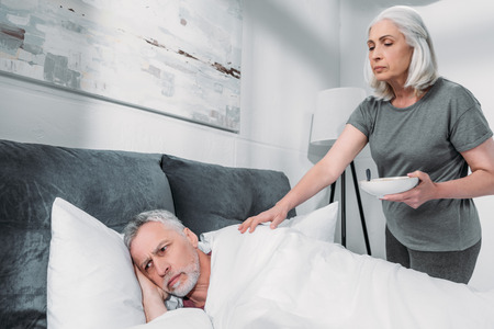 woman taking care of sick husband in bed