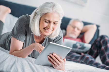 smiling senior woman using tablet while resting on bed