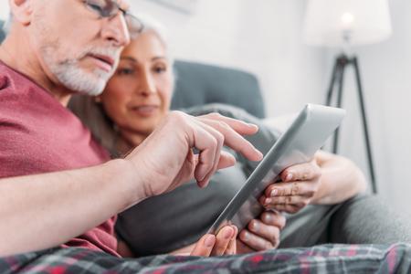 paar met digitale tablet samen rusten in bed