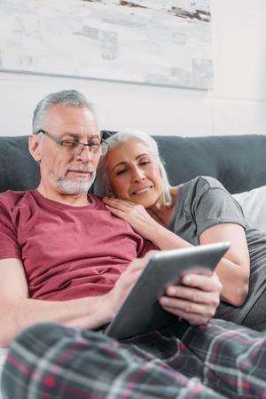 Ltere Paare mit digitaler Tablette , die im Bett zusammen stillsteht Standard-Bild - 84372570