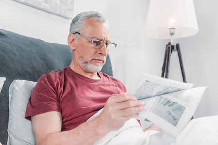 man reading newspaper while lying in bed at home Banco de Imagens
