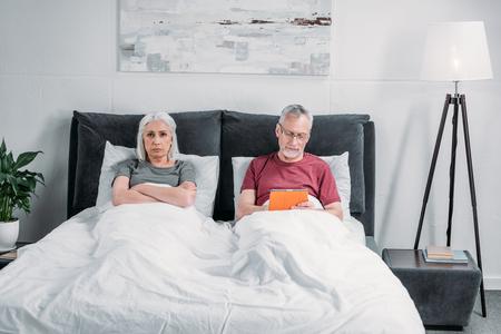 Mann, der Tablette während mürrische Frau im Bett liegend verwendet Standard-Bild - 84372576