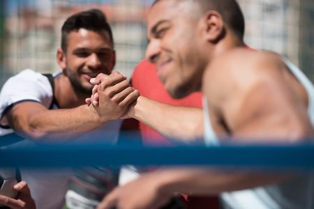 african american handshake: Multicultural men sitting on stadium before training