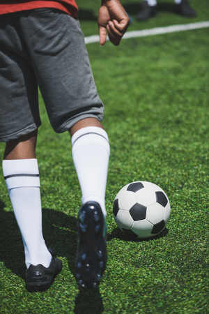 soccer player training with ball on soccer pitch